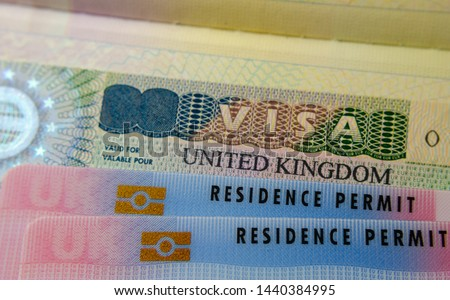 United Kingdom BRP (Biometrical Residence Permit) cards for Tier 2 work visa placed on top of UK VISA sticker in the passport. Close up photo.  Сток-фото ©