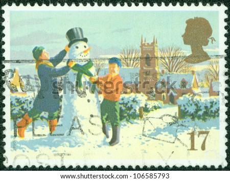 UNITED KINGDOM - CIRCA 1990: A British Used Christmas Postage Stamp showing Children Building a Snowman, circa 1990