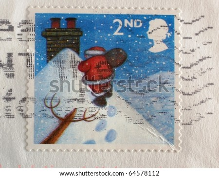 UNITED KINGDOM - CIRCA 2004: A second (2nd) class stamp printed in the United Kingdom shows image of Santa Claus walking towards a chimney in the snow (Scott 2008 2244), circa 2004