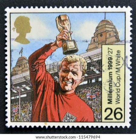 UNITED KINGDOM - CIRCA 1999: A stamp printed in Great Britain shows Bobby Moore with World Cup, circa 1999