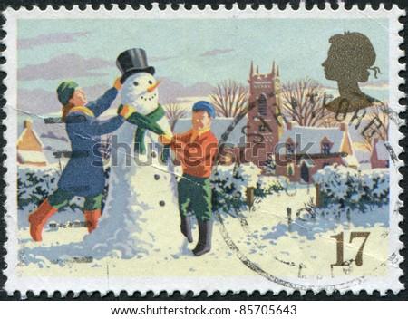 UNITED KINGDOM - CIRCA 1990: A stamp printed in the United Kingdom, shows Building snowman, Christmas, circa 1990 - stock photo