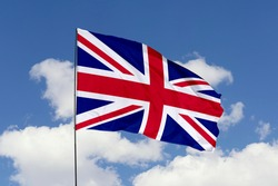 United Kingdom flag isolated on the blue sky with clipping path. close up waving flag of United Kingdom. flag symbols of United Kingdom.