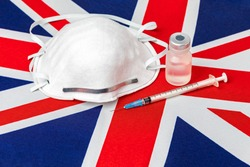 United Kingdom flag, n95 face mask, needle syringe and vial. Concept of UK Covid-19 coronavirus vaccine distribution, supply shortage and healthcare crisis