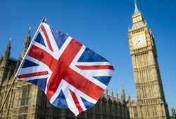 United Kingdom flag waving in bright blue sky in front of the Houses of Parliament at Westminster Palace with Big Ben