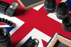 United Kingdom national flag with top view of personal photographer equipment and tools on white wooden table, copy space.
