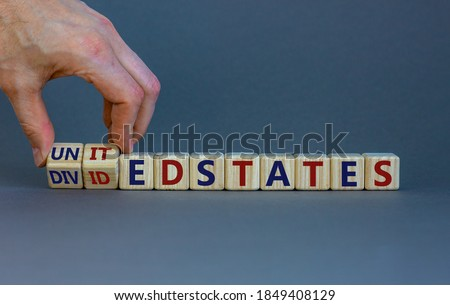 United or divided states of Amerika. Male hand flips wooden cubes and changes the inscription 'United States' to 'Divided States'. Beautiful grey background, copy space. Stok fotoğraf ©