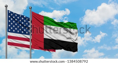 United States and United Arab Emirates flag waving in the wind against white cloudy blue sky together. Diplomacy concept, international relations. #1384508792