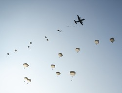 United States Army Soldiers and Paratroopers descending in the sky, from an Air Force C-130 military aircraft during an Airborne Operation.