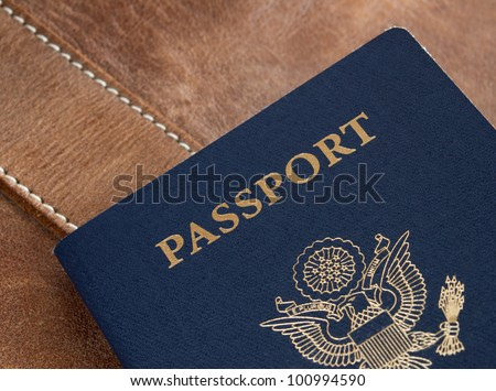 United States blue passport on leather backdrop.