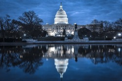 United States Capitol Building at night with mirror reflection over the reflection pool - Washington DC, United States of America