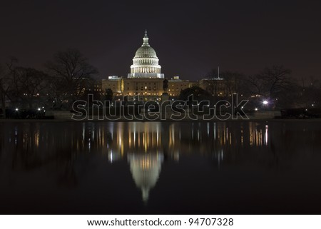 United States Capitol Building at night with the dome reflection on the pool, in Washington DC