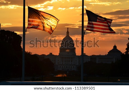 United States Capitol building silhouette and US flags at sunrise - Washington DC