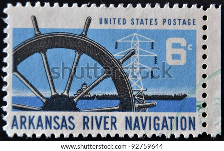 UNITED STATES - CIRCA 1968: A stamp printed in USA dedicated to arkansas river navigation, shows ship wheel, power transmission tower and barge, circa 1968