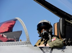 United States Fighter Pilot in full gear sitting in a fighter jet