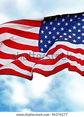 United States flag flying against a cloudy blue sky.