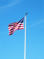 United States flag on a pole with a bright blue sky