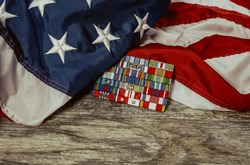 United States Flag with Military Service Ribbons on Distressed Wood Background