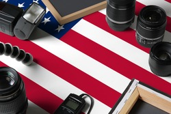 United States national flag with top view of personal photographer equipment and tools on white wooden table, copy space.