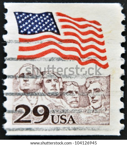 UNITED STATES OF AMERICA - CIRCA 1991: A stamp printed in the USA shows American flag waving above Mt. Rushmore, circa 1991 - stock photo