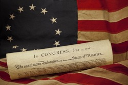 United States of America Declaration of Independence dated July 4, 1776 lying on an American flag. The flag, popularly attributed to Betsy Ross, was designed during the American Revolutionary War.