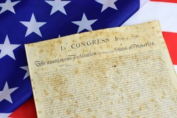 United States of America Declaration of Independence with Betsy Ross flag on the background.