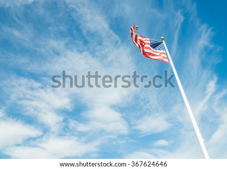 United States of America flag with cloudy blue sky
