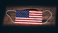 United States of America National Flag at medical, surgical, protection... mask on black wooden background. Coronavirus Covid–19, Prevent infection, illness or flu. State of Emergency, Lockdown