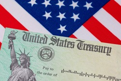 United States Treasury check and American flag. Concept of stimulus payment, tax refund and federal government grants, loans, benefits and assistance