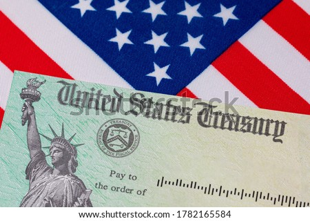 United States Treasury check and American flag. Concept of stimulus payment, tax refund and federal government grants, loans, benefits and assistance Сток-фото ©