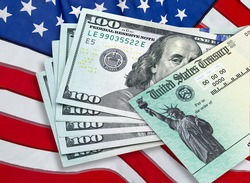 United States Treasury check with 100 dollars US currency and American flag. Coronavirus economic impact stimulus payments or IRS tax refund.