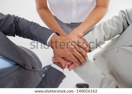United team piling up their hands in the workplace - stock photo