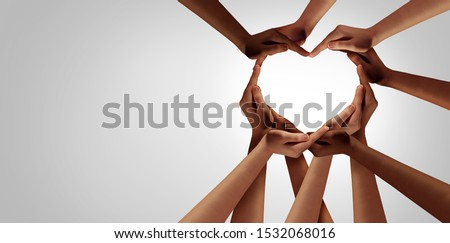 Unity and diversity partnership as heart hands in a group of diverse people connected together shaped as a support symbol expressing the feeling of teamwork and togetherness. stock photo
