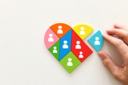 Unity and diversity partnership concept. heart shaped puzzle and group of diverse miniature people connected