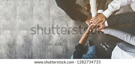 Unity and teamwork. Business people putting their hands together, top view, copy space