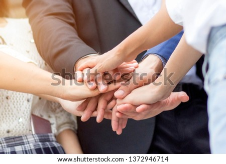 Unity and teamwork concept; Close up top view of business people putting their hands together. Stack of hands. #1372946714