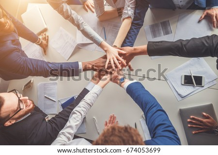 Unity concept. Close-up of people holding hands together while sitting around the desk