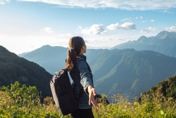 Unity with nature, a young female tourist in the mountains. Arms out to hug the horizon. Tourist with a backpack hikes in the mountains