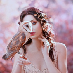 unity with nature, portrait photography of cute girl with fair skin and white owl, lady with wavy black hair in beige shiny dress hides half her face, gold flowers in hair, pink delicate shades