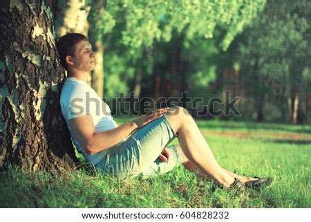 Unity with nature! Relaxing man is dreaming under a tree with eyes closed meditating enjoying the warm evening sunset in profile