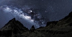 Universe space shot of nebula and milky way on hill under amazing starry blue night sky, large ravine. Silhouette of Snow Mountain Grand Canyon of U Thong Stone Mill Suphanburi, Stonehenge of Thailand