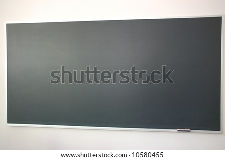 University blackboard with chalk and eraser on ledge - stock photo