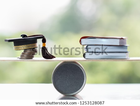 University Education learning abroad international Ideas. Student Graduation cap on stack coins, books on wood round box balance. Concept of study requires cost money saving for success in school
