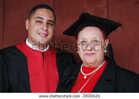 University graduate in robes with his grandmother. Grandmother wearing his cap.