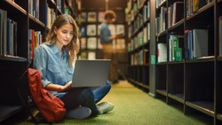 University Library: Gifted Beautiful Caucasian Girl Sitting On Floor, Uses Laptop, Writes Notes for Paper, Essay, Study for Class Assignment. Diverse Group of Students Learning, Studying for Exams.