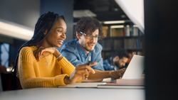 University Library: Gifted Black Girl uses Laptop, Smart Classmate Explains and Helps Her with Class Assignment. Happy Diverse Students Talking, Learning, Studying Together for Exams