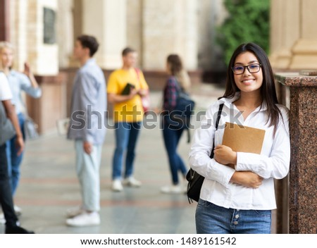 University life. Happy asian girl holding books and smiling, resting between classes Stock photo ©