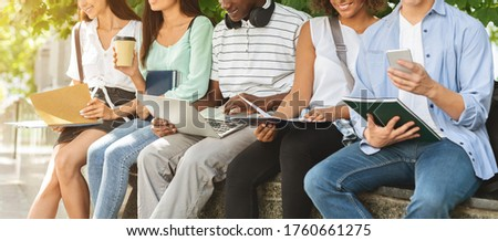 University life. Students preparing for lessons, sitting in campus with books and devices, cropped image, panorama Stock photo ©