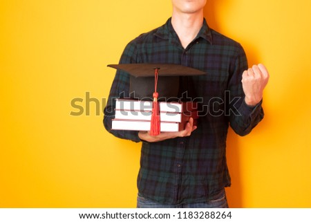 University man is happy with graduation on yellow background   #1183288264