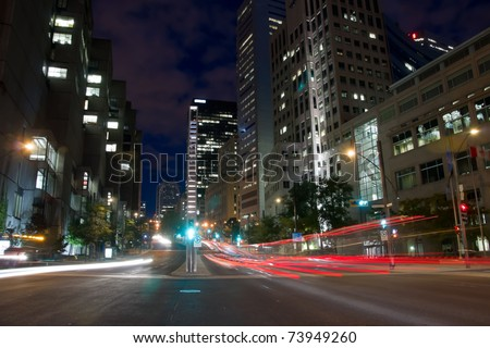 University Street in Montreal with silhouette cars with red rear light and traffic light, early morning to dusk,with office buildings background.