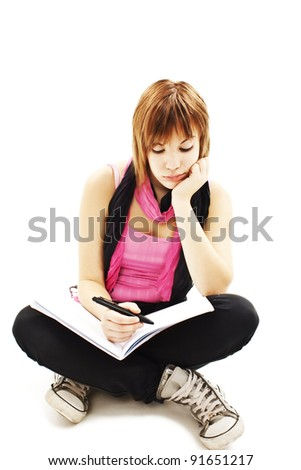 University student bored, frustrated and overwhelmed by studying homework. Young woman sitting down on floor isolated on white background.